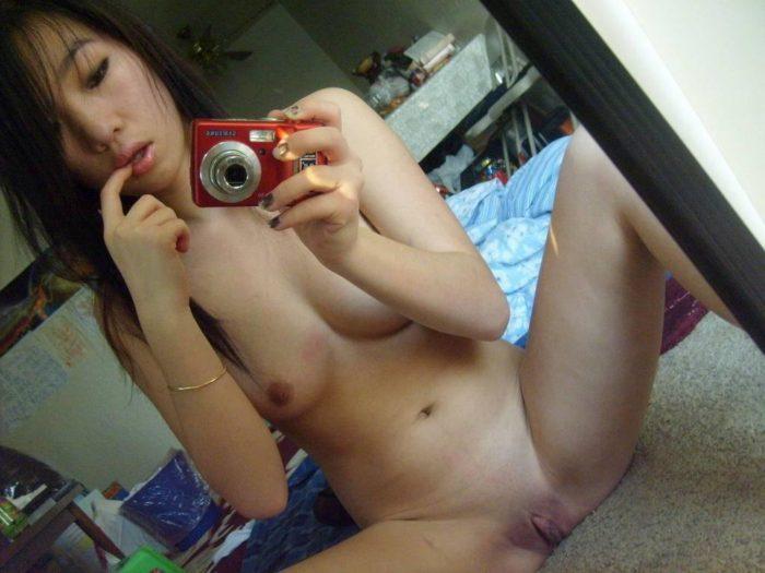 Une belle meuf asiatique en selfie dans le miroir de sa chambre