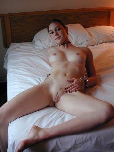 Une jolie punk rousse nue dans une chambre d'hôtel
