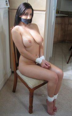 Une esclave sexuelle aux gros seins attachée sur une chaise
