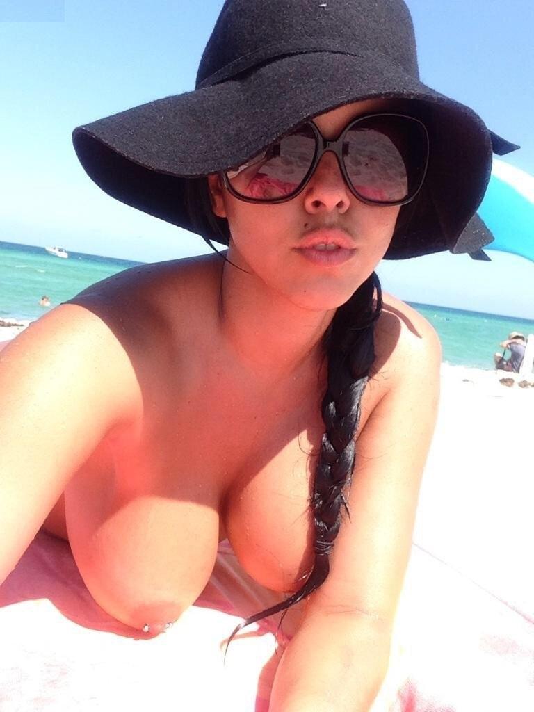 Une jolie beurette se prend en selfie sur la plage les seins nus et piercés
